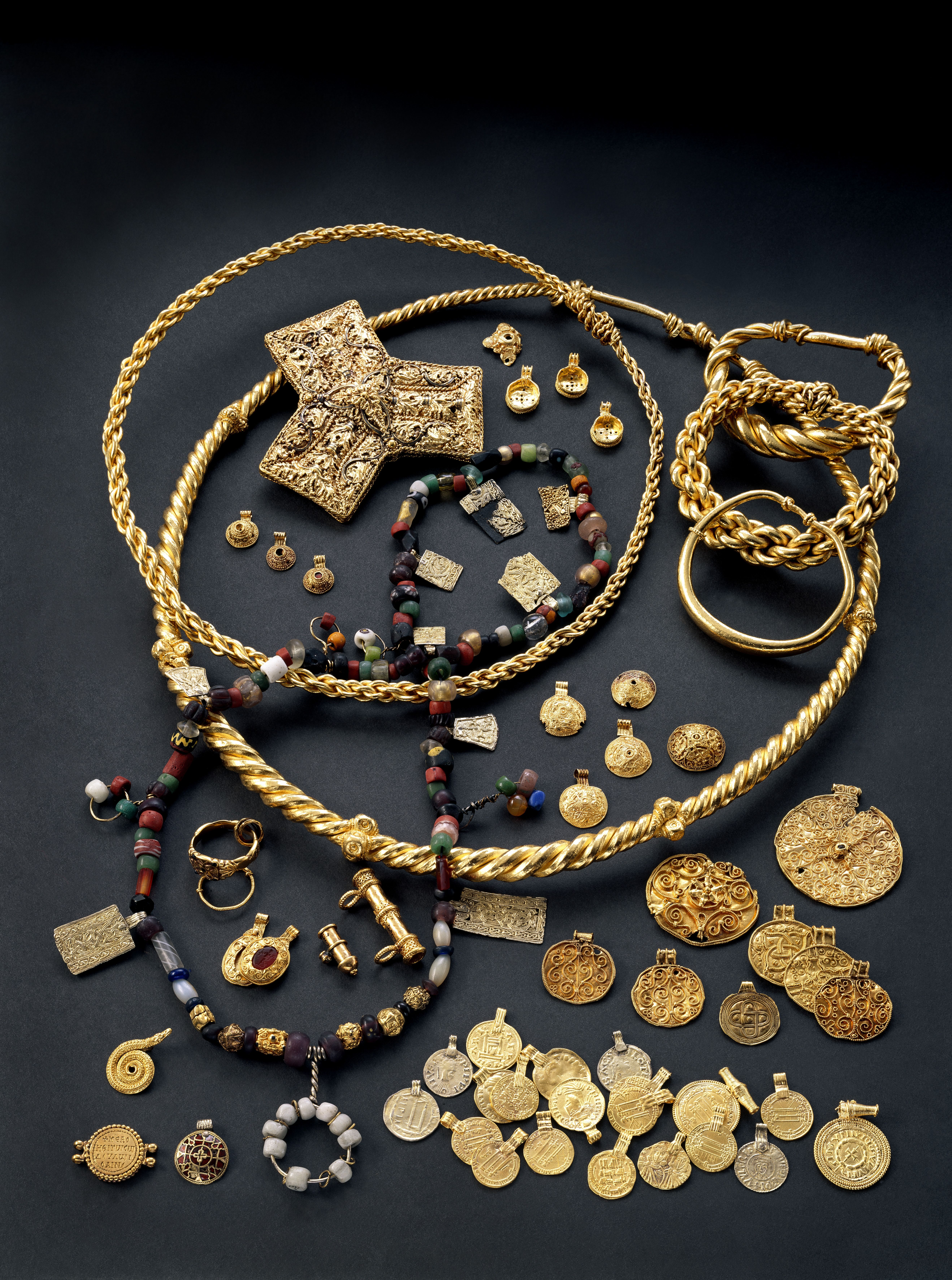 Hoenfunnet. Skattefunn fra Øvre Eiker i Buskerud. Skandinavias største gullskatt. Består av importerte mynter og beslag, samt skandinaviske gullsmykker. De importerte gjenstandene er alle omgjort til spenner eller hengesmykker. Skatten er trolig nedlagt mellom 875 og 900. Ove Holst/Kulturhistorisk museum