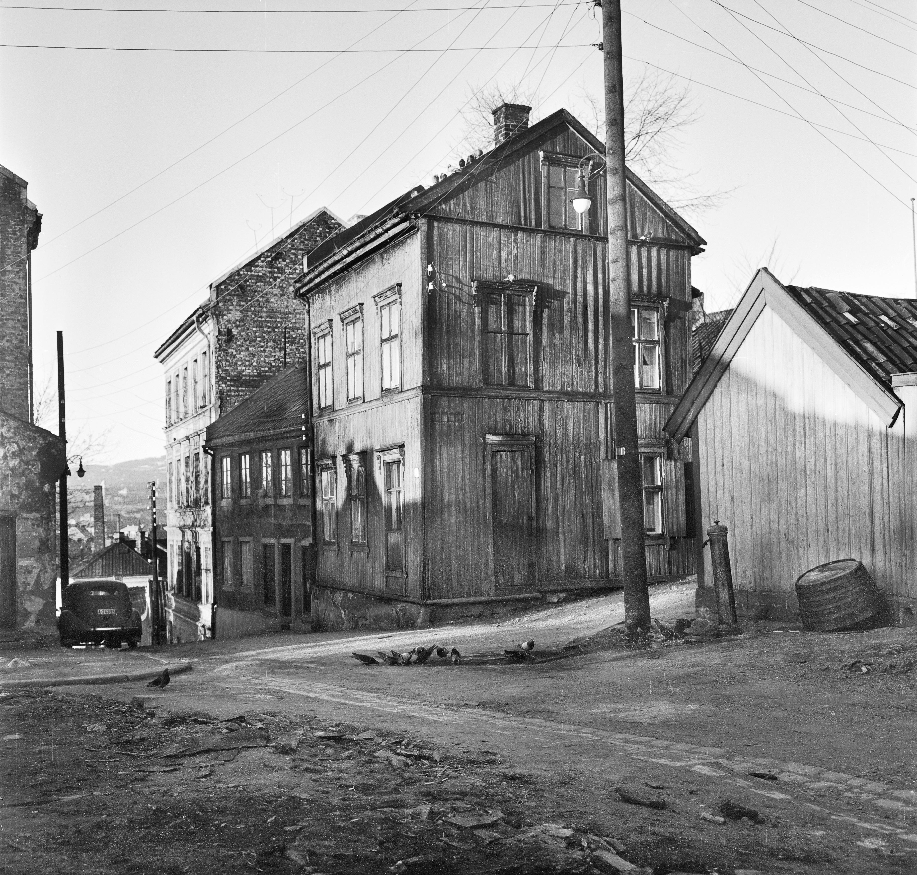 Trehusbebyggelse med vannpost på Enerhaugen, krysset Langleiken og Johannesgata i 1959. Foto: Peter Anker, Oslo Museum OB.A1088.